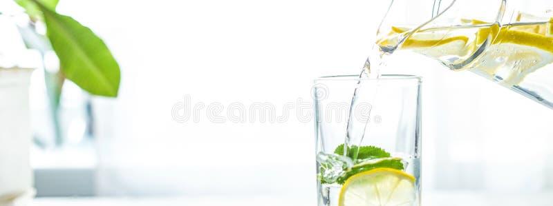 Έκχυση ενός ποτηριού του νερού με το λεμόνι, τον πάγο και τη μέντα σε έναν άσπρο πίνακα στοκ εικόνα