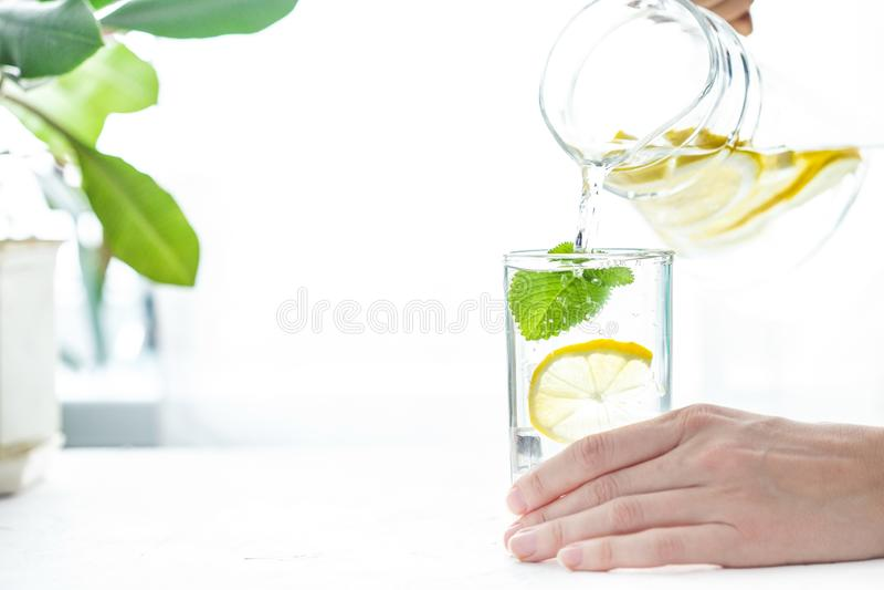 Έκχυση ενός ποτηριού του νερού με το λεμόνι, τον πάγο και τη μέντα σε έναν άσπρο πίνακα στοκ φωτογραφίες
