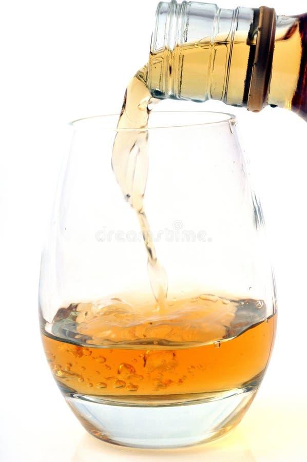 Έκχυση ενός ποτηριού του ουίσκυ στην κινηματογράφηση σε πρώτο πλάνο σε ένα άσπρο υπόβαθρο στοκ φωτογραφίες