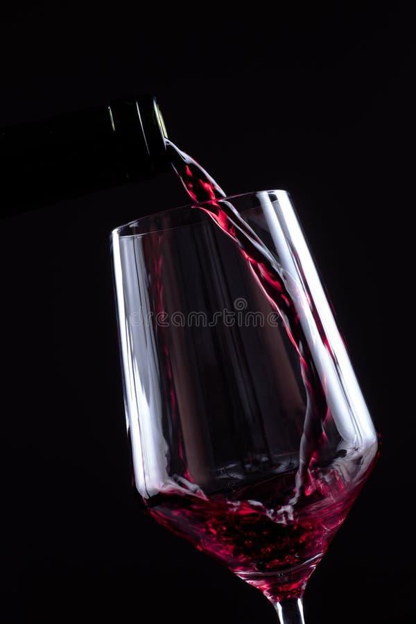Έκχυση κόκκινου κρασιού wineglass από ένα μπουκάλι στο μαύρο υπόβαθρο Επιλογές σχεδίου καταλόγων κρασιού με το copyspace στοκ εικόνες με δικαίωμα ελεύθερης χρήσης