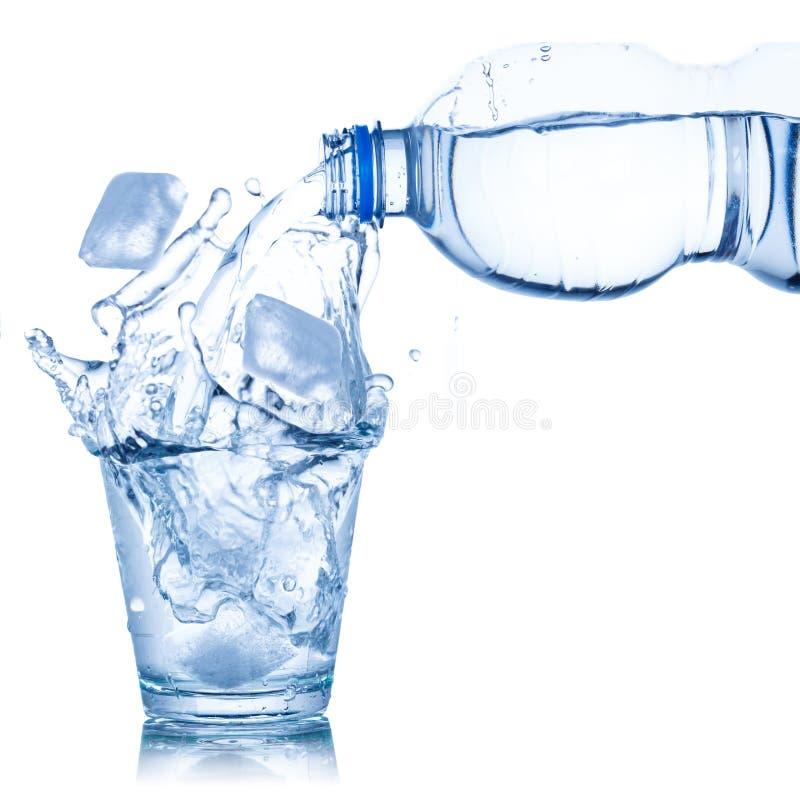 Έκχυση νερού στον κύβο πάγου γυαλιού που απομονώνεται στο λευκό στοκ φωτογραφία με δικαίωμα ελεύθερης χρήσης