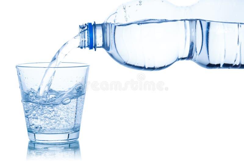 Έκχυση νερού στο γυαλί που απομονώνεται στο λευκό στοκ εικόνα