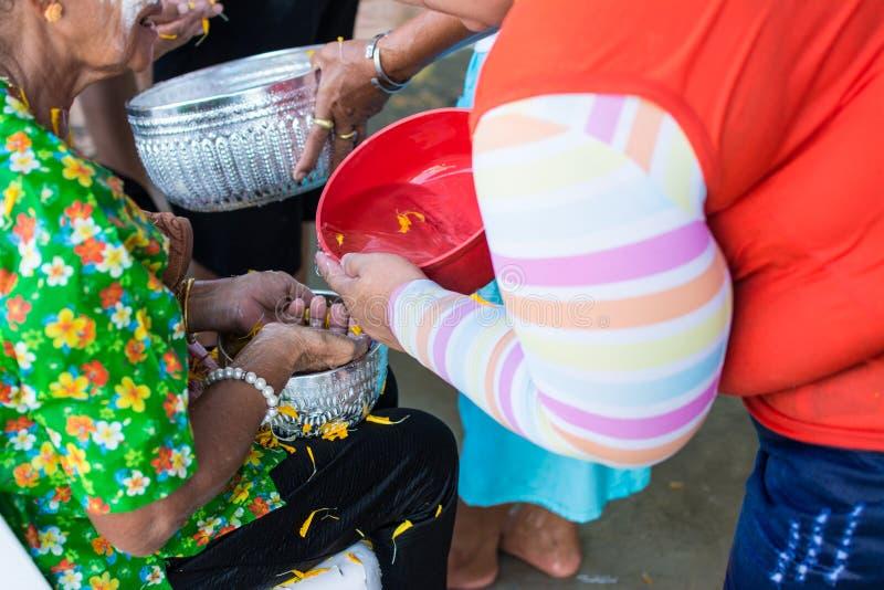 Έκχυση νερού στο ηλικιωμένο άνθρωπο στην παράδοση φεστιβάλ Songkran Ταϊλάνδης στοκ εικόνες