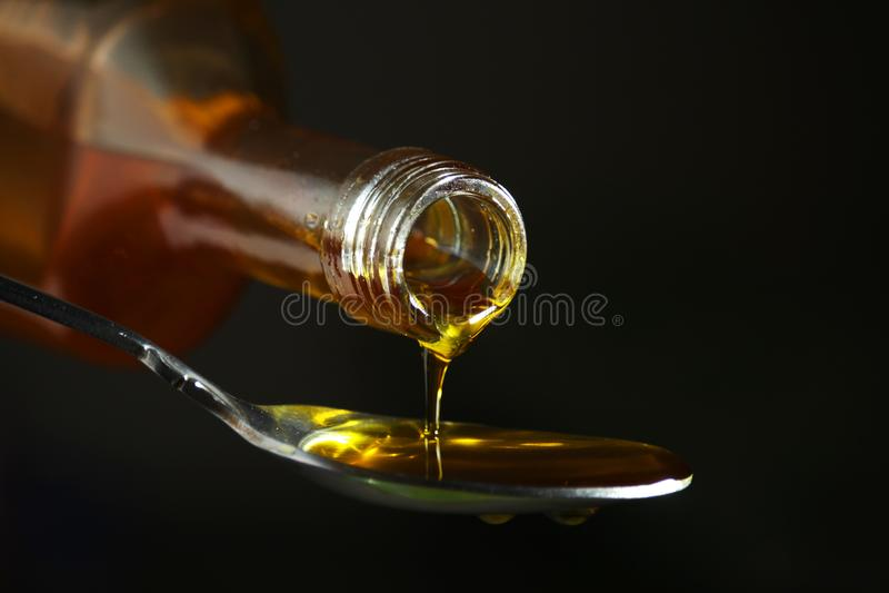 Έκχυση πετρελαίου στο κουτάλι από το μπουκάλι στοκ εικόνες