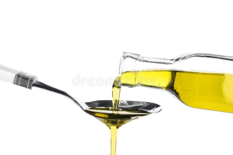 Έκχυση του ελαιολάδου από το μπουκάλι γυαλιού στο κουτάλι στο άσπρο υπόβαθρο στοκ φωτογραφία με δικαίωμα ελεύθερης χρήσης