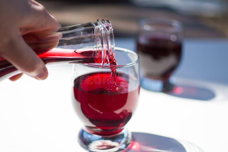 Έκχυση του κόκκινου κρασιού σε ένα γυαλί στοκ εικόνες