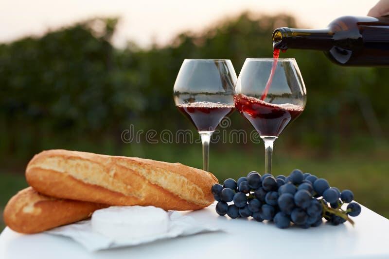 Έκχυση του κόκκινου κρασιού στα γυαλιά στοκ εικόνες