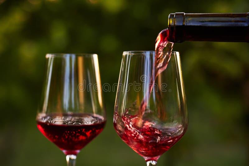 Έκχυση του κόκκινου κρασιού στα γυαλιά στοκ φωτογραφία