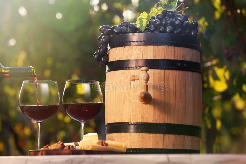Έκχυση του κόκκινου κρασιού στο γυαλί στον πίνακα στοκ εικόνα