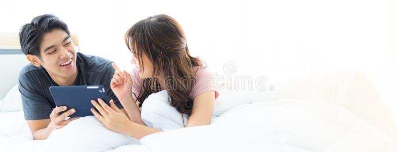 Έμβλημα ενός ασιατικού ζεύγους που βάζει στο κρεβάτι που χρησιμοποιεί Διαδίκτυο στοκ φωτογραφία