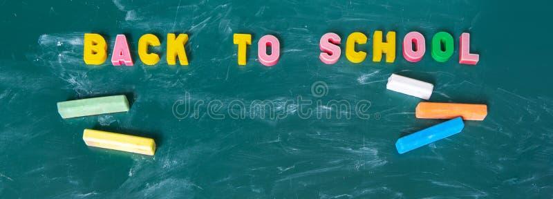 Έμβλημα Επιγραφή ΠΙΣΩ στο ΣΧΟΛΕΙΟ Ακόμα ζωή με τις σχολικές προμήθειες Πολύχρωμη κιμωλία Πίνακας στον πίνακα κιμωλίας κιμωλίας o στοκ φωτογραφία με δικαίωμα ελεύθερης χρήσης