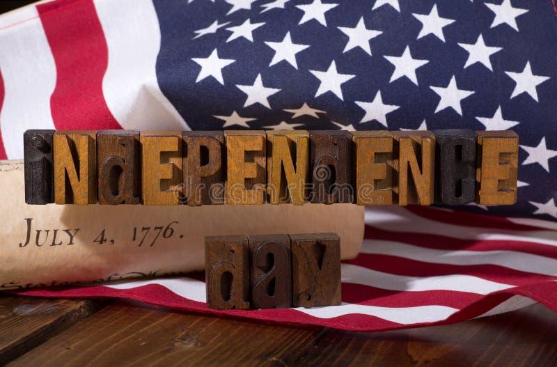 Έμβλημα ημέρας της ανεξαρτησίας με τη αμερικανική σημαία και τη Διακήρυξη ο στοκ φωτογραφίες