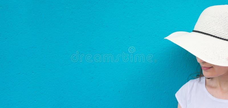 έμβλημα μακρύ Αρκετά νέα καυκάσια γυναίκα στην άσπρη μπλούζα καπέλων ήλιων αχύρου χρωματισμένο στο τυρκουάζ υπόβαθρο τοίχων lifes στοκ εικόνες