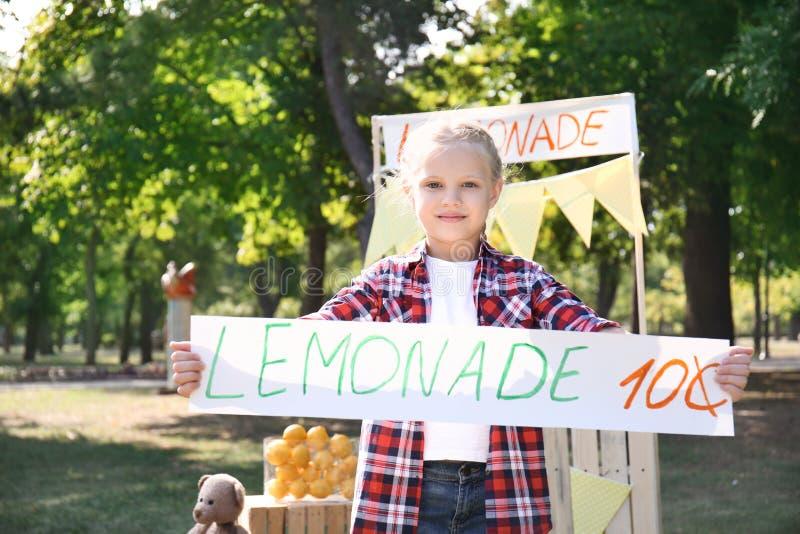 Έμβλημα τιμών εκμετάλλευσης μικρών κοριτσιών κοντά στη στάση λεμονάδας στο πάρκο στοκ εικόνες