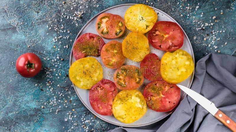 Έμβλημα τροφίμων Νόστιμες κόκκινες και κίτρινες ντομάτες με το άλας και καρυκεύματα σε ένα στρογγυλό πιάτο r στοκ φωτογραφία με δικαίωμα ελεύθερης χρήσης