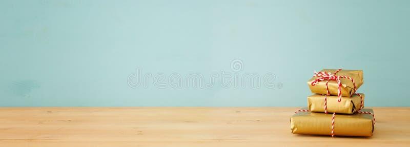 έμβλημα των χειροποίητων τυλιγμένων κιβωτίων δώρων πέρα από τον ξύλινο πίνακα στοκ εικόνες