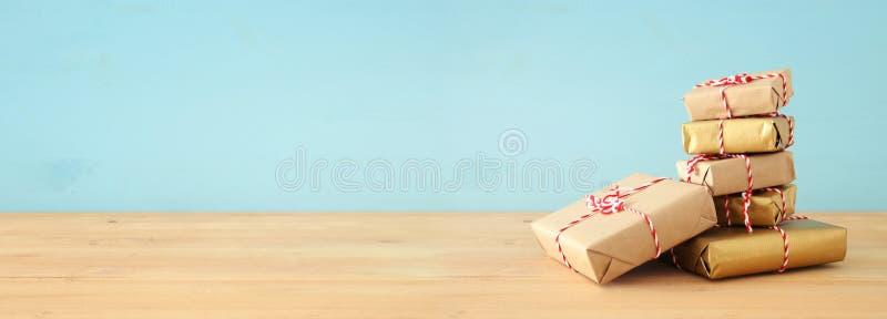 έμβλημα των χειροποίητων τυλιγμένων κιβωτίων δώρων πέρα από τον ξύλινο πίνακα στοκ φωτογραφία με δικαίωμα ελεύθερης χρήσης