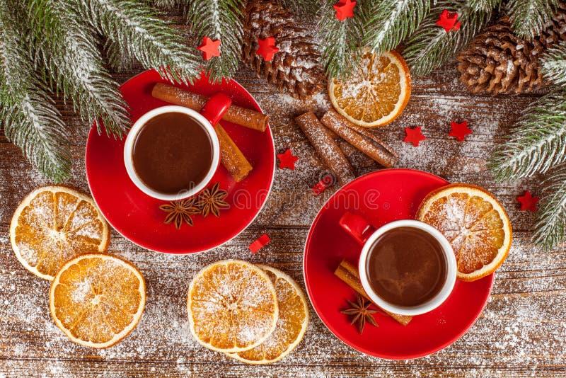Έμβλημα Χριστουγέννων με το πράσινο δέντρο, κώνοι, κόκκινα φλυτζάνια με την καυτές σοκολάτα, το πορτοκάλι και την κανέλα στο καφε στοκ εικόνα