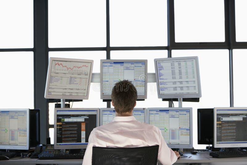 Έμπορος αποθεμάτων που εξετάζει τις πολλαπλάσιες οθόνες υπολογιστή στοκ εικόνα με δικαίωμα ελεύθερης χρήσης