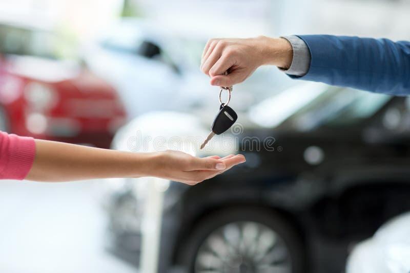 Έμπορος αυτοκινήτων που δίνει τα κλειδιά στη γυναίκα στοκ εικόνα με δικαίωμα ελεύθερης χρήσης