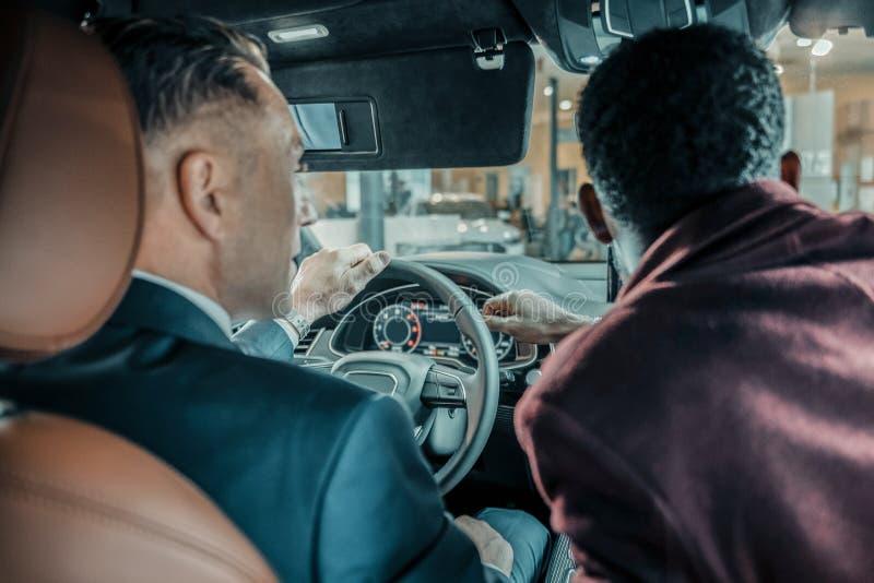 Έμπορος αυτοκινήτων που βοηθά τον πελάτη του κατά τη διάρκεια του τεστ δοκιμής στοκ εικόνες