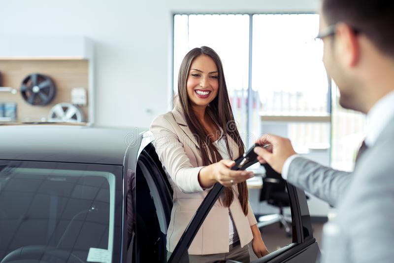 Έμπορος αυτοκινήτων που δίνει το κλειδί στο νέο ιδιοκτήτη αυτοκινήτων στοκ εικόνες
