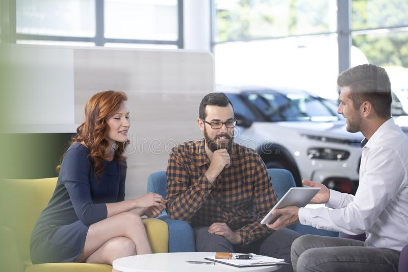 Έμπορος αυτοκινήτων που παρουσιάζει μια προσφορά στους ευτυχείς πελάτες του σε ένα showro αυτοκινήτων στοκ εικόνες