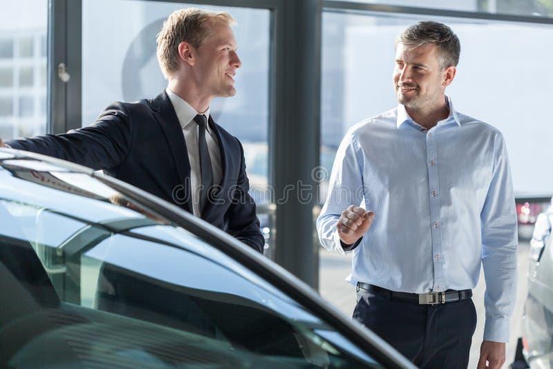 Έμπορος αυτοκινήτων που παρουσιάζει όχημα στοκ εικόνα