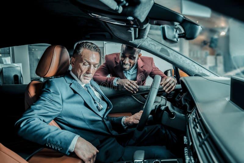 Έμπορος αυτοκινήτων που ρωτά τον πελάτη του για τις εντυπώσεις στοκ εικόνα με δικαίωμα ελεύθερης χρήσης