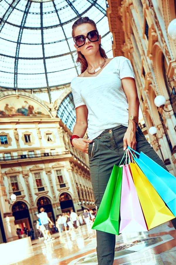 Έμπορος μόδας eyeglasses με τις τσάντες αγορών σε Galleria στοκ εικόνες