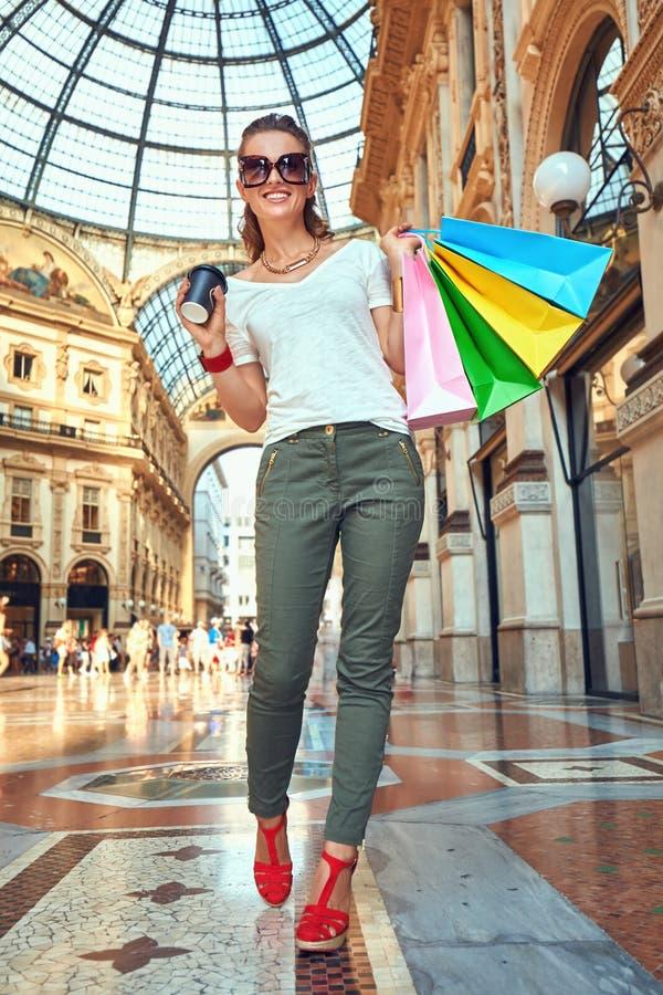 Έμπορος μόδας με τις τσάντες αγορών και φλυτζάνι καφέ σε Galleria στοκ εικόνα με δικαίωμα ελεύθερης χρήσης