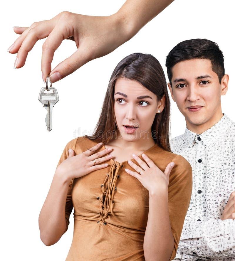 Έμπορος που δίνει τα κλειδιά στο ευτυχές νέο ζεύγος στοκ εικόνες