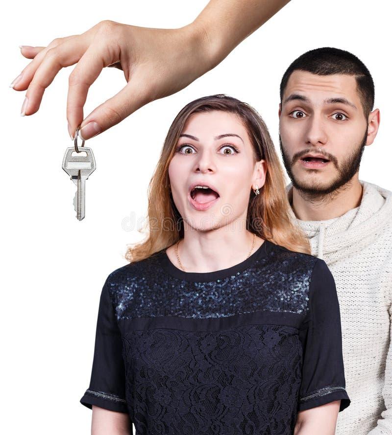 Έμπορος που δίνει τα κλειδιά στο ευτυχές νέο ζεύγος στοκ φωτογραφίες