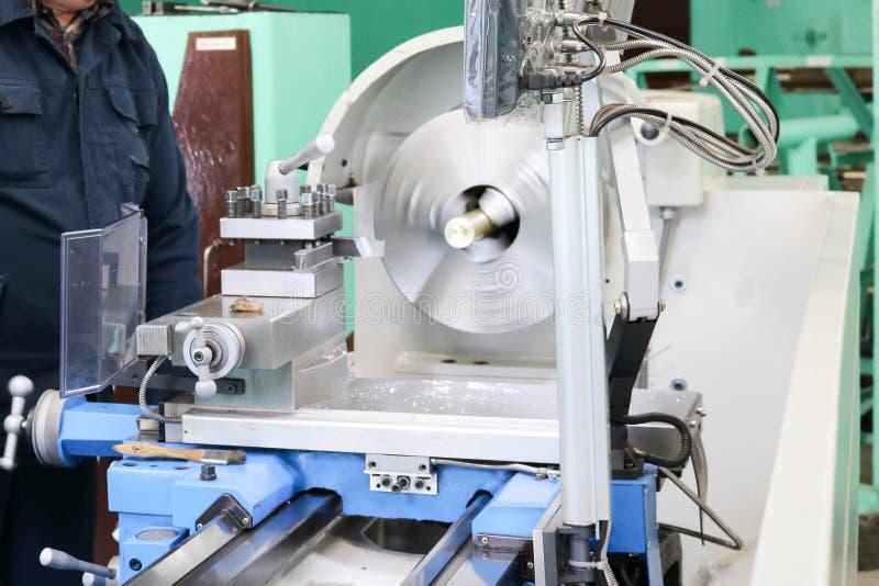 Ένας άνδρας εργαζόμενος λειτουργεί σε έναν μεγαλύτερο τόρνο κλειδαράδων σιδήρου μετάλλων, εξοπλισμός για τις επισκευές, εργασία μ στοκ εικόνες