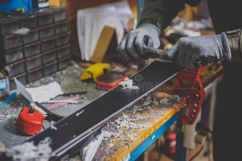 Ένας άνδρας εργαζόμενος σε ένα εργαστήριο υπηρεσιών σκι επισκευάζει την επιφάνεια ολίσθησης των σκι Κινηματογράφηση σε πρώτο πλάν στοκ φωτογραφίες