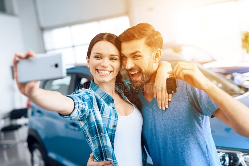 Ένας άνδρας και μια γυναίκα selfie κοντά στο νέο αυτοκίνητό τους στοκ εικόνα με δικαίωμα ελεύθερης χρήσης