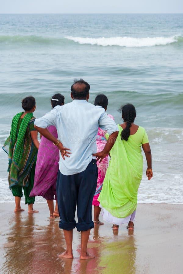 Ένας άνδρας και τέσσερις γυναίκες, ξυπόλυτοι, βλέμμα προς την τραχιά θάλασσα στοκ φωτογραφία