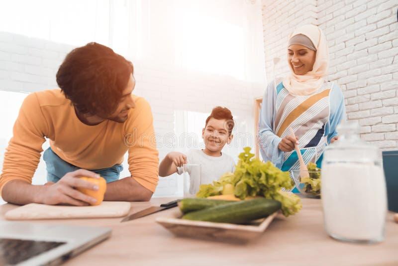 Ένας άνδρας, μια γυναίκα σε ένα hijab και ο γιος τους στην κουζίνα στοκ εικόνες με δικαίωμα ελεύθερης χρήσης
