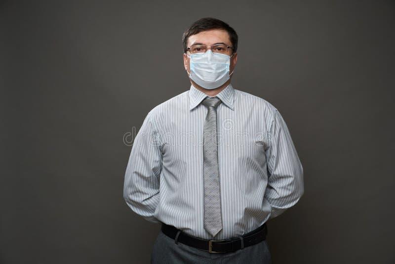 Ένας άνδρας ντυμένος επιχειρηματίας που ποζάρει σε ένα στούντιο σε γκρι φόντο, μάσκα ιατρικού προσώπου, γυαλιά, ένα ελαφρύ ριγέ π στοκ φωτογραφία με δικαίωμα ελεύθερης χρήσης