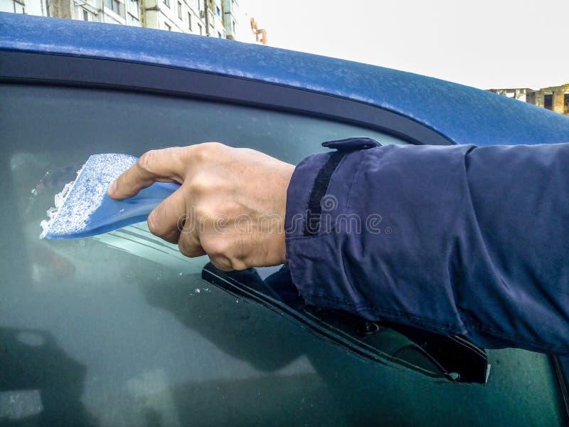 Ένας άνδρας ξετυλίγει παγετό με ένα πλαστικό αποξέστωμα από το πλαϊνό παράθυρο ενός μπλε αυτοκινήτου Χέρι χωρίς γάντια στο κρύο Ο στοκ φωτογραφία