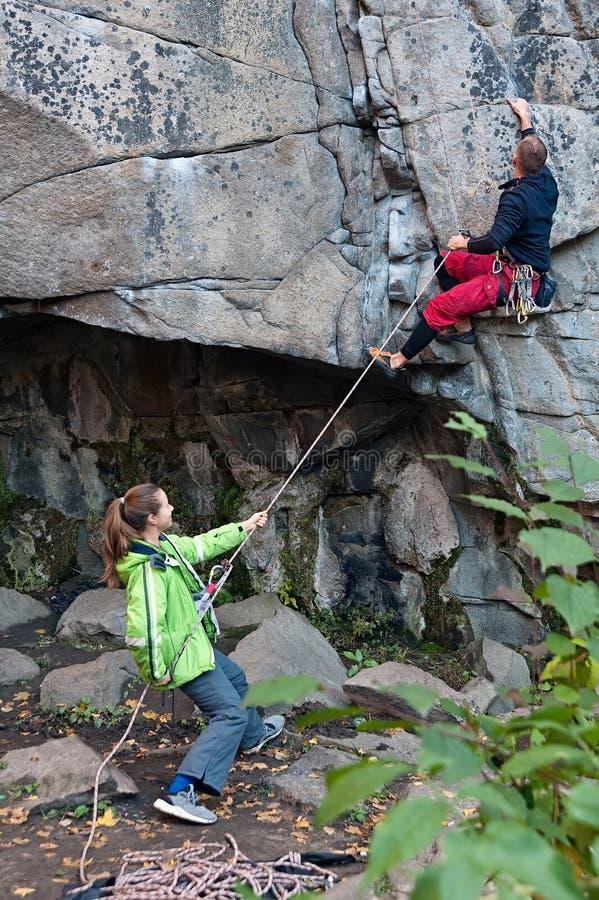 Ένας άνδρας που αναρριχούνται στο βουνό και μια γυναίκα που τραβά το σχοινί για τον στην Ουκρανία στοκ εικόνες