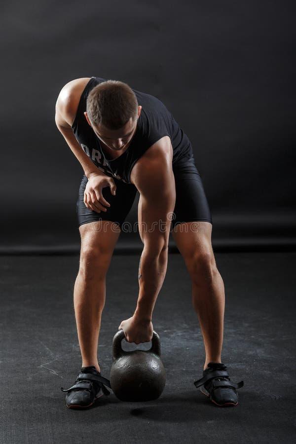 Ένας άνδρας σλόγκαν με μαύρα ρούχα γυμναστικής με kettlebell στοκ φωτογραφία