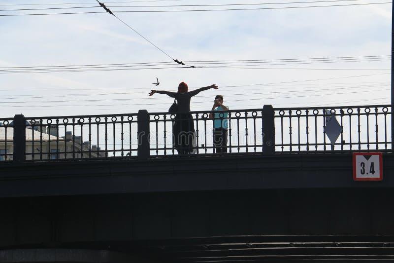 Ένας άνδρας στη γέφυρα φωτογραφίζει στο τηλέφωνο μια νέα γυναίκα στοκ φωτογραφίες με δικαίωμα ελεύθερης χρήσης