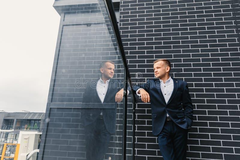 Ένας άντρας με κοστούμι κοιτάζει την απόσταση στο μπαλκόνι στοκ φωτογραφία