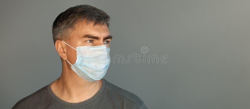 Ένας άντρας με προστατευτική μάσκα και γκρι μπλουζάκι στοκ εικόνα