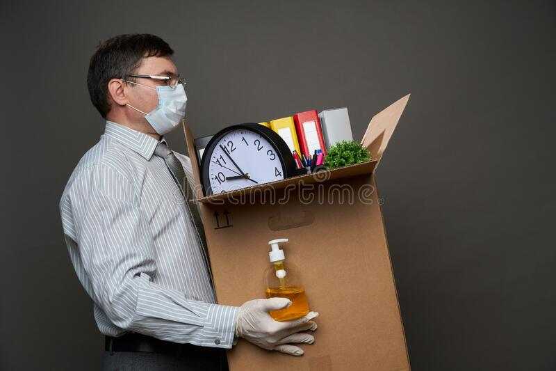 Ένας άντρας ντυμένος επιχειρηματίας κρατά ένα κουτί με πράγματα γραφείου, έγγραφα, κομπιουτεράκια, που ποζάρουν στο στούντιο σε γ στοκ εικόνα