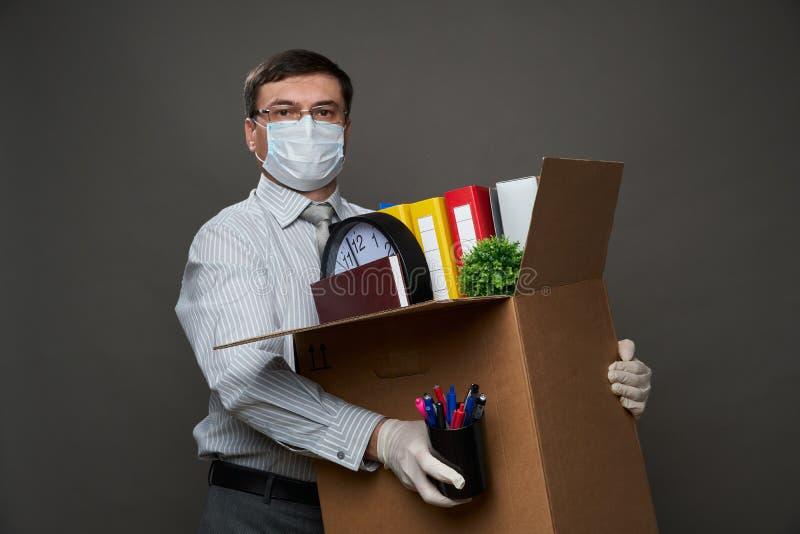 Ένας άντρας ντυμένος επιχειρηματίας κρατά ένα κουτί με πράγματα γραφείου, έγγραφα, ποζάρουν στο στούντιο σε γκρίζο φόντο, μάσκα ι στοκ φωτογραφίες με δικαίωμα ελεύθερης χρήσης