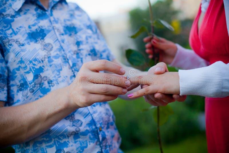 Ένας άνδρας προτείνει στη γυναίκα, που βάζει το δαχτυλίδι στο δάχτυλό της στοκ εικόνες