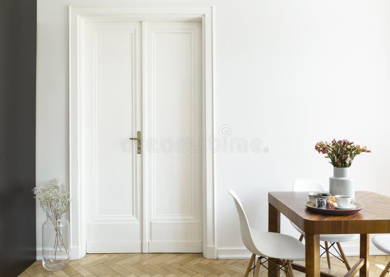 Ένας άσπρος τοίχος με τη διπλή πόρτα δίπλα σε έναν ξύλινο πίνακα προγευμάτων και καρέκλες σε ένα εσωτερικό τραπεζαρίας Πραγματική στοκ φωτογραφίες