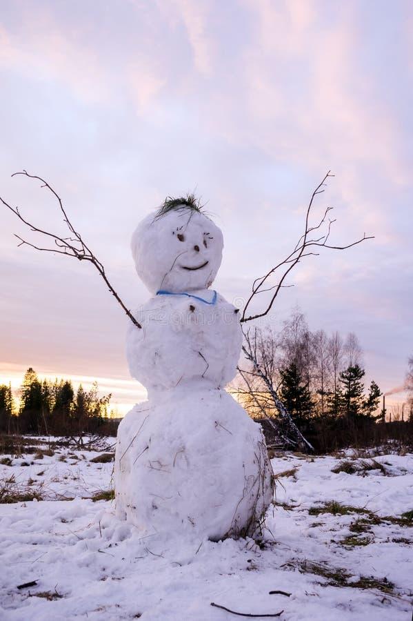 Ένας άσχημος χιονάνθρωπος με τους αυξημένους βραχίονας-κλάδους στέκεται σε ένα χιονώδες λιβάδι στο ηλιοβασίλεμα στοκ εικόνα